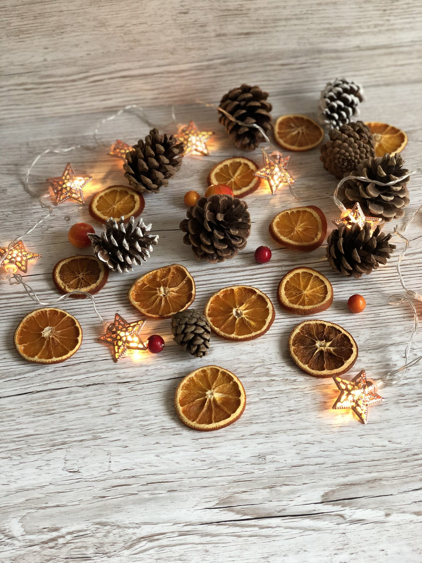 Dried orange slices, pine cones and fairy lights on a wooden background.