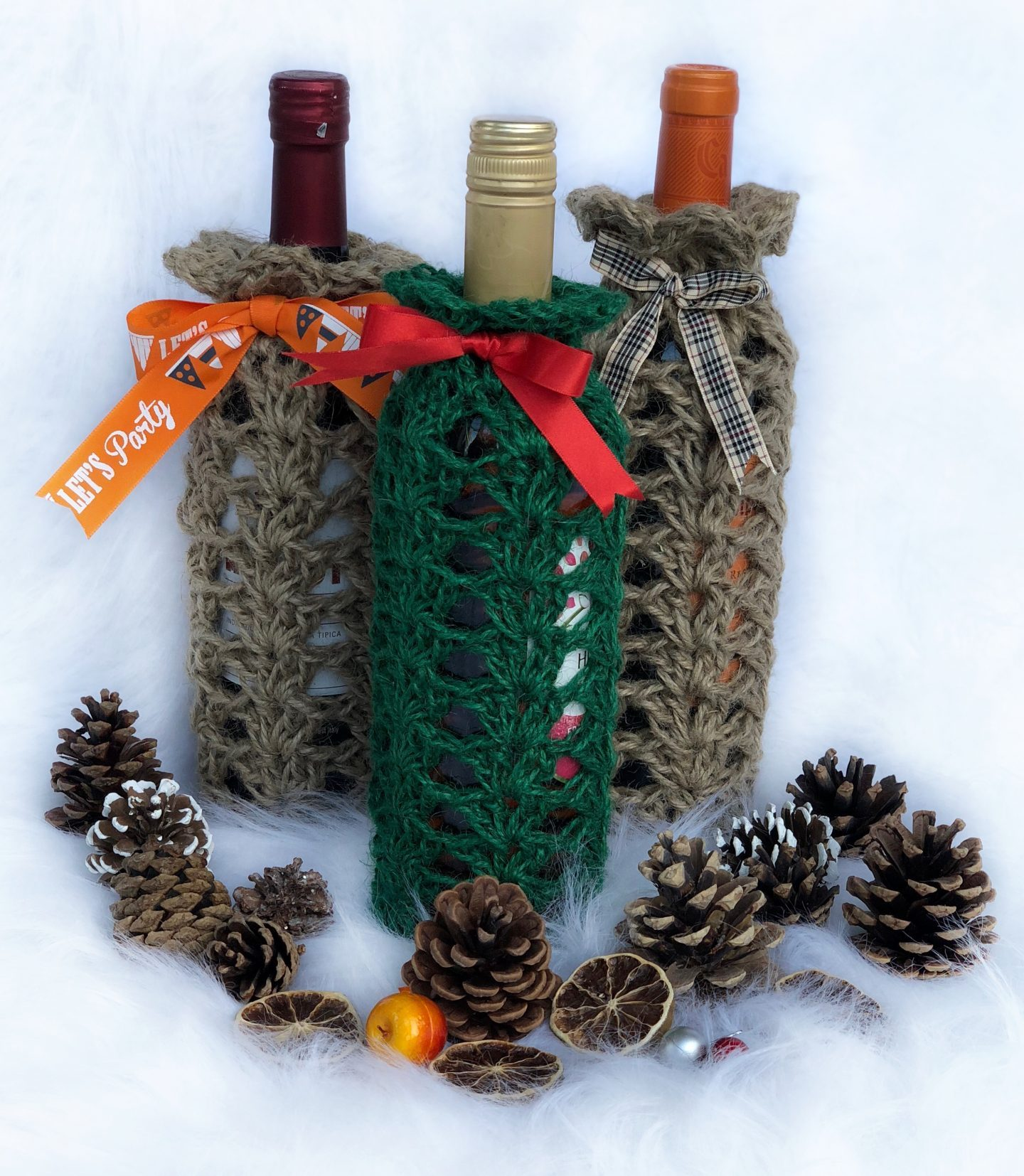 Crochet wine bottle covers with pine cones and dried orange slices.